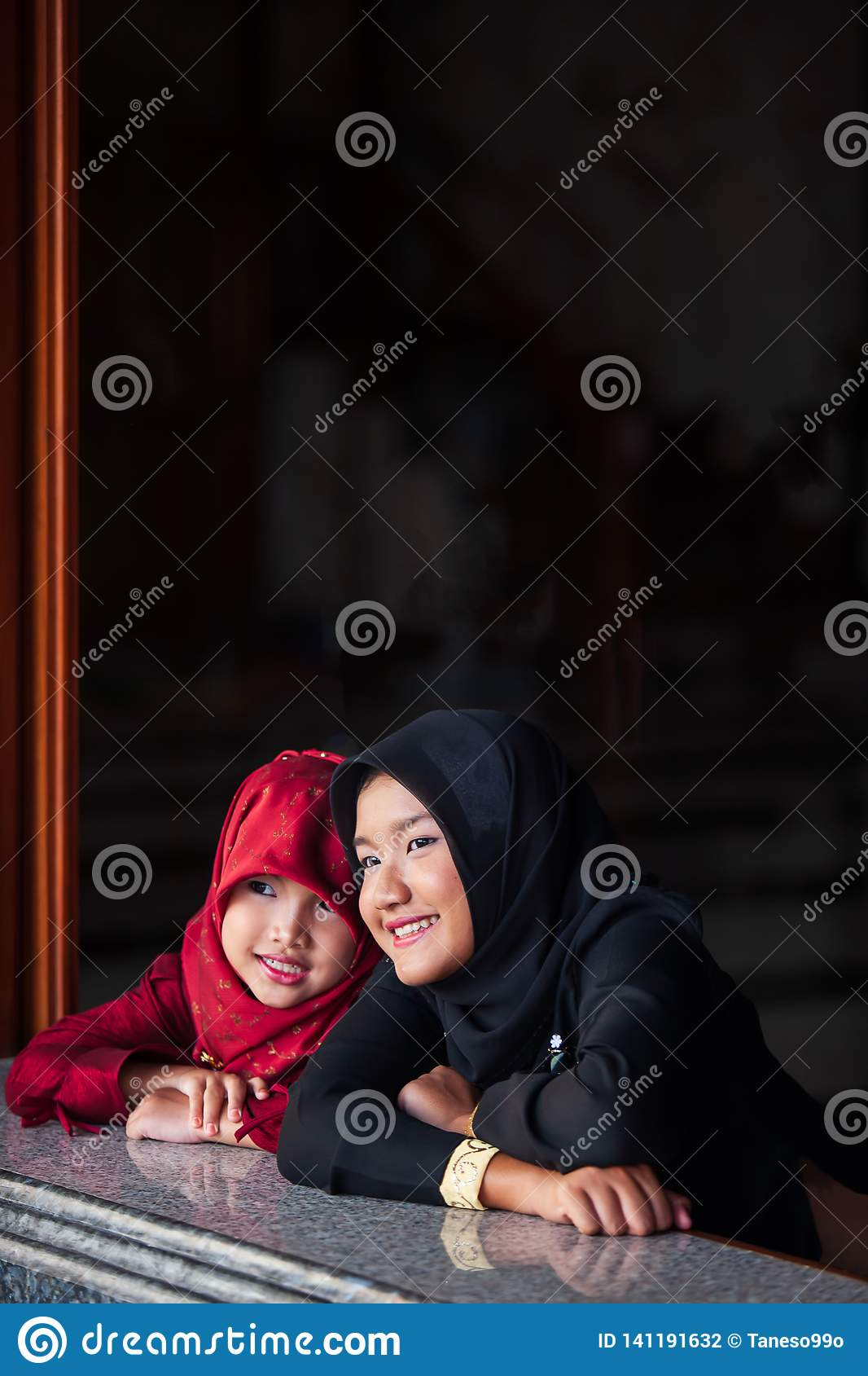 Couple adorable muslim girl in traditional clothing, black and red hijab or niqab and abaya smiling and watching out the window.