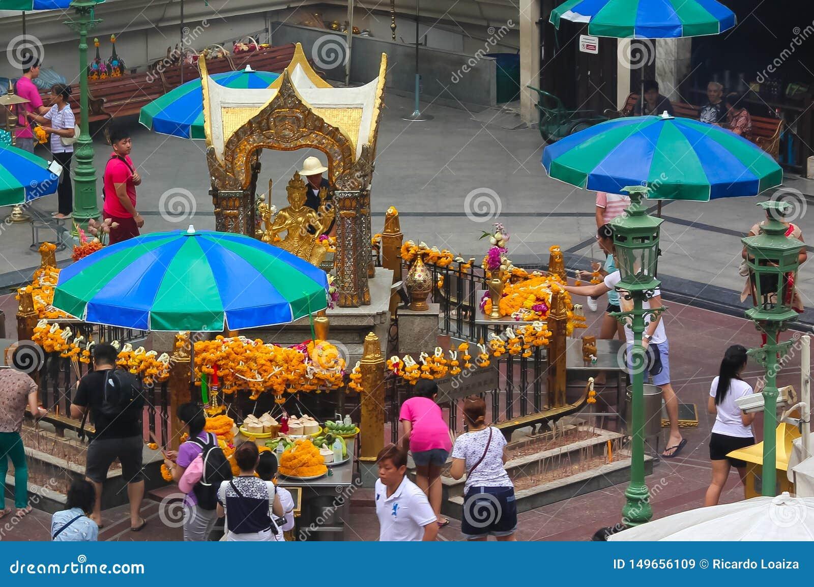 Bangkok Thailand - April 31, 2014 Folk som ber på ett altare av dyrkan till Phra Phrom, gud av den visade världen i staden