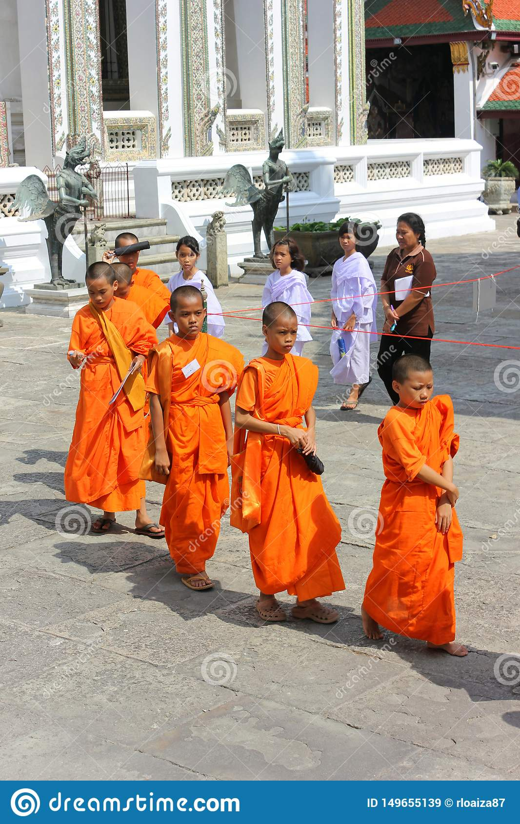 Bangkok, Thailand - April 29, 2014. Group of Asian monks walking through the temple of the Emerald Buddha in Thailand