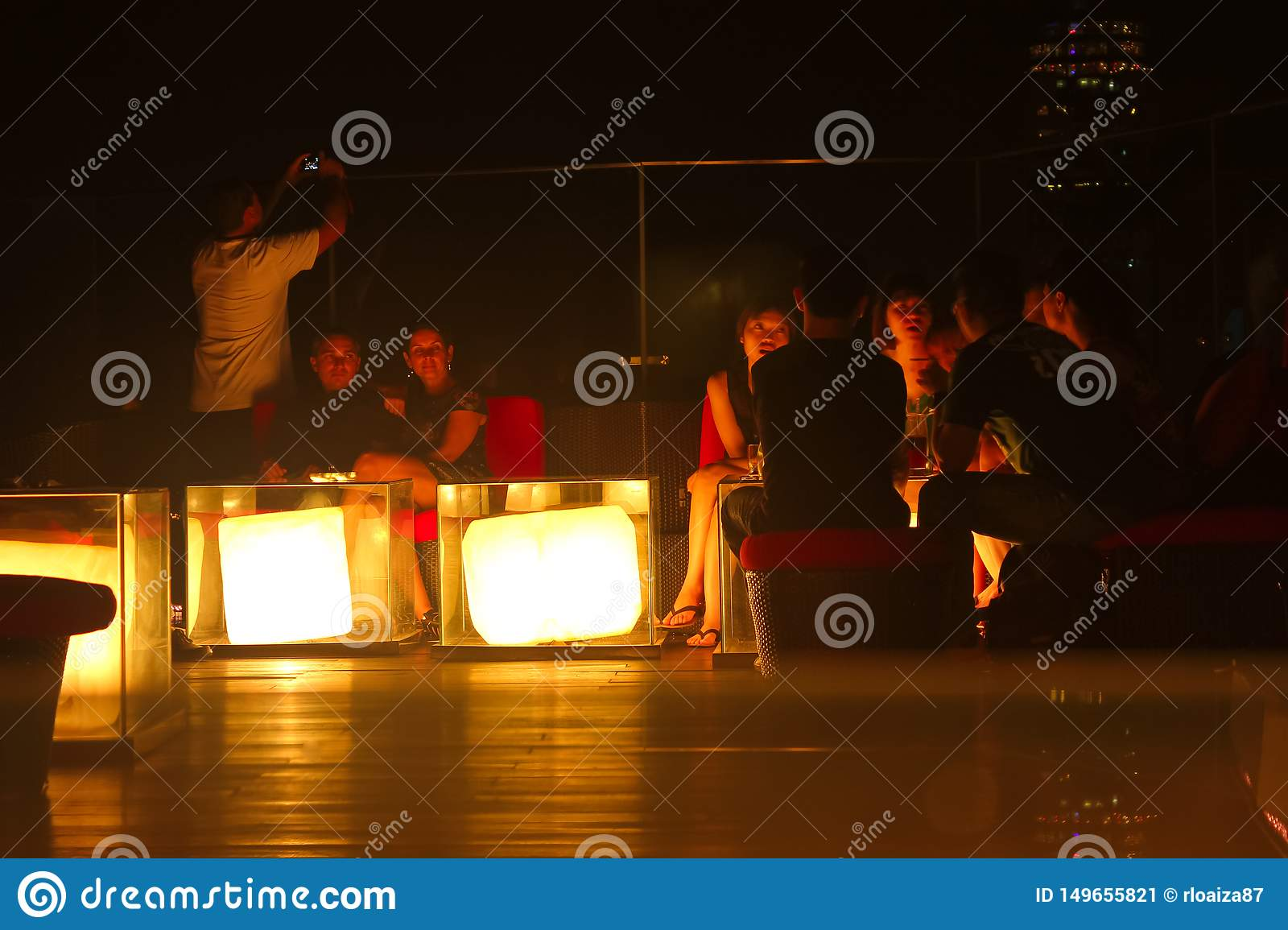 Bangkok, Thailand - April 28, 2014. Meeting of people enjoying the night and the view on a terrace of the city of Bangkok,