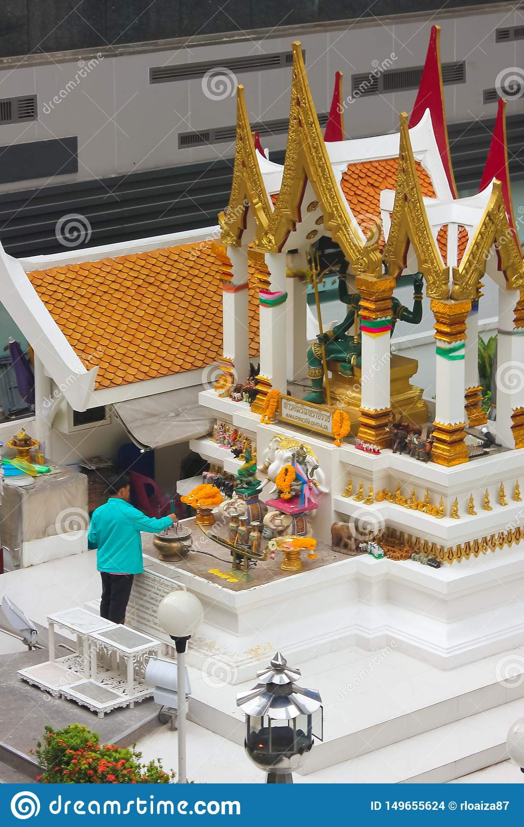Bangkok, Thailand - April 31, 2014. Man making an offering at Amarindradhiraja shrine in the city of Bangkok