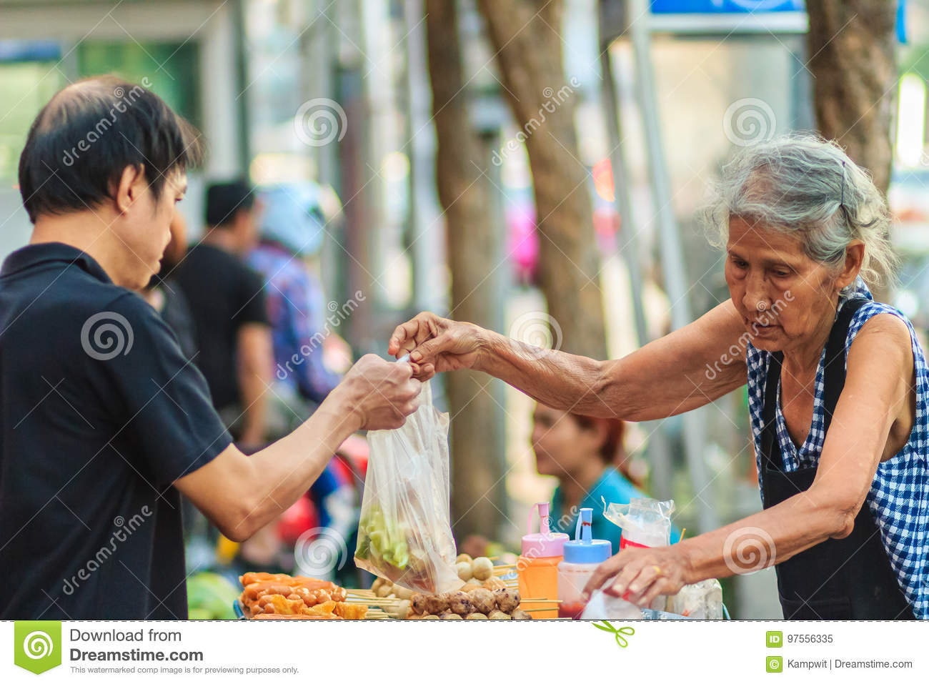 Bangkok, Thailand - April 23, 2017: Unidentified old woman street vendor is selling fried meat balls to her customer.