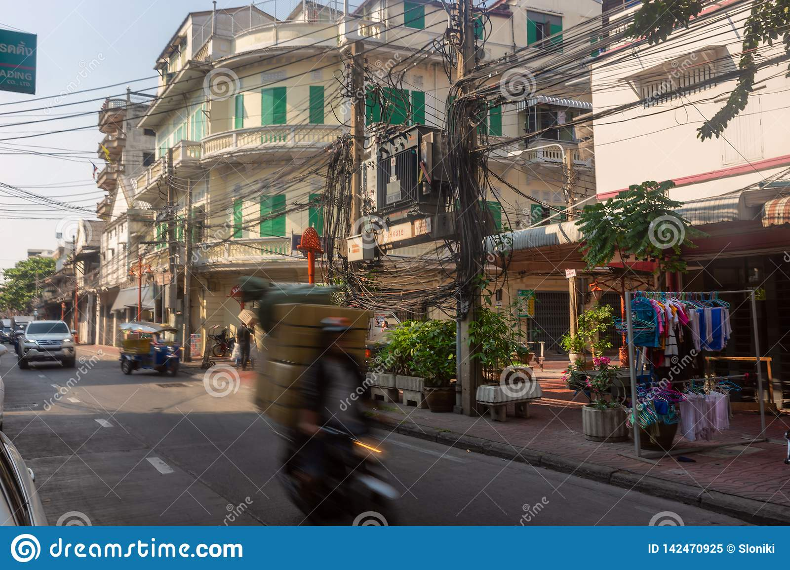 Bangkok, Thailand - February 14 2019 : Moving Bike with boxes on the china town street .Twisted electrical wires on the streets of