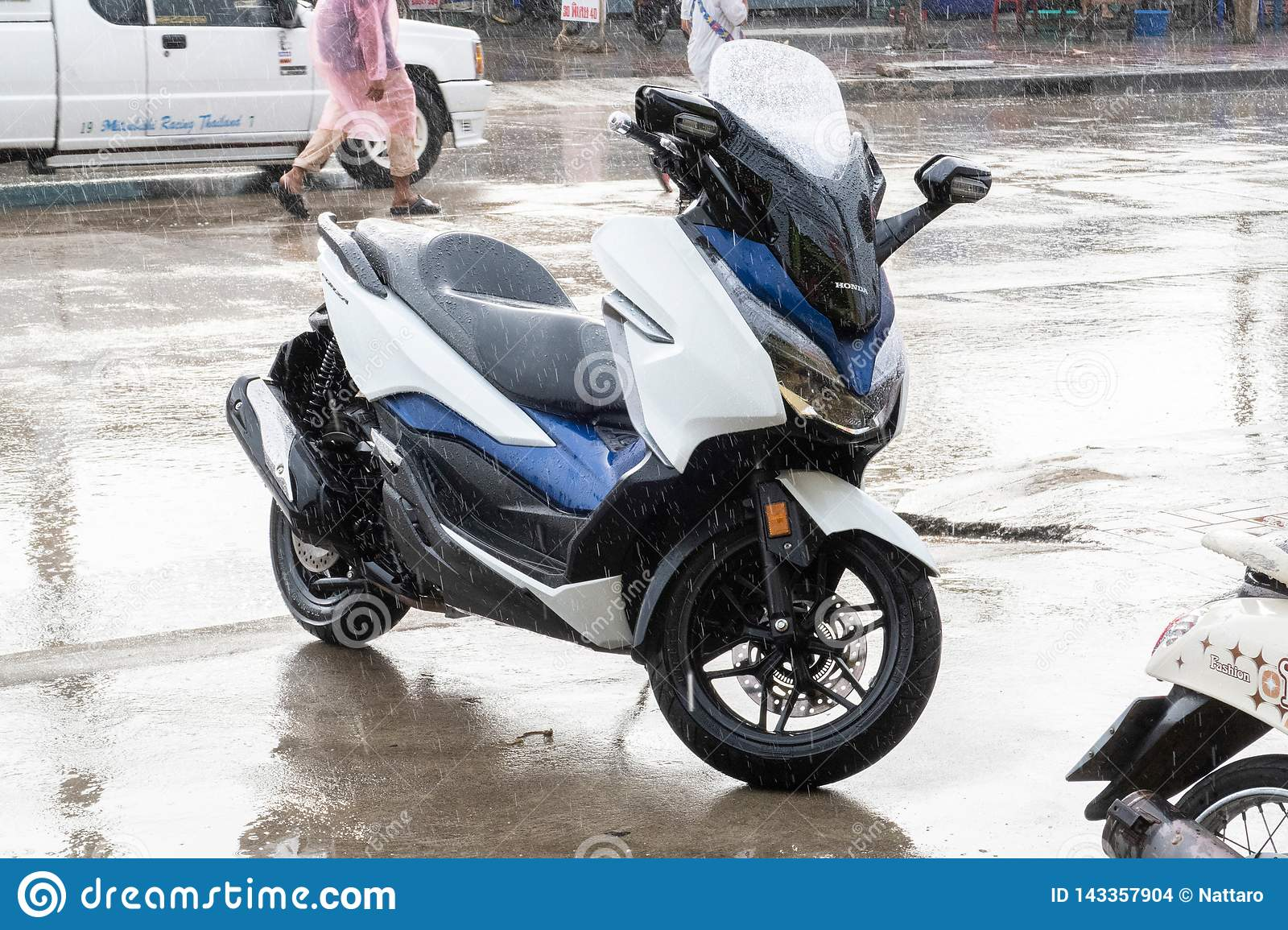 Side view of white-Blue 2018 Honda Forza 300 motorcycle parking on side walk in raining day