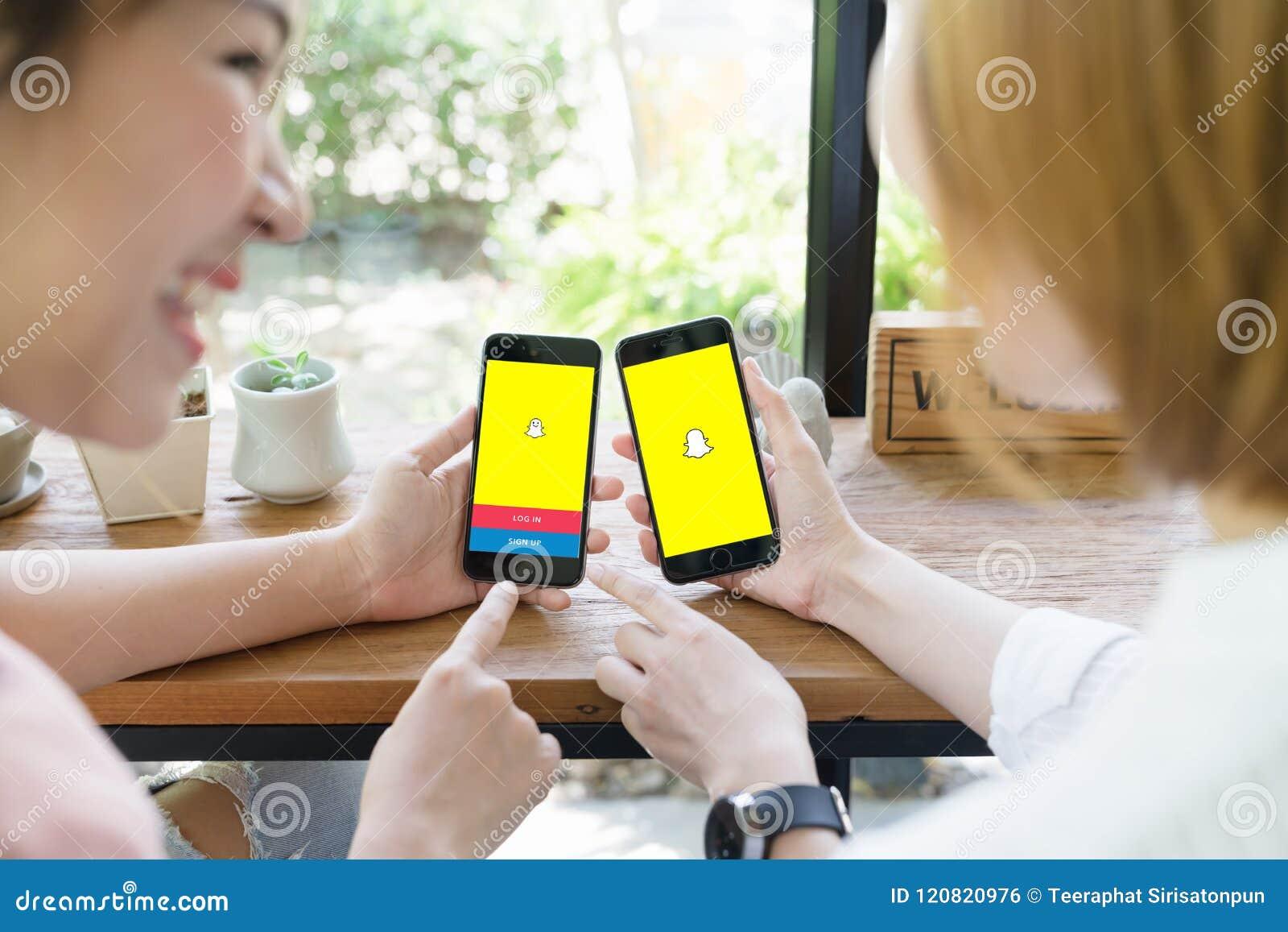 BANGKOK, THAILAND - JUNI 04.2018: Aziatische vrouw twee die snapchat toepassing op iphone gebruiken Snapchat is online sociaal me