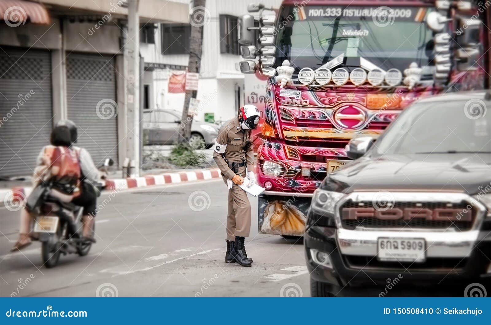 BANGKOK, THAILAND - 12. JUNI: Ungenannte Verkehrspolizistfragen eine Karte zu nicht identifiziertem Verkehrssünder auf Straße Pet