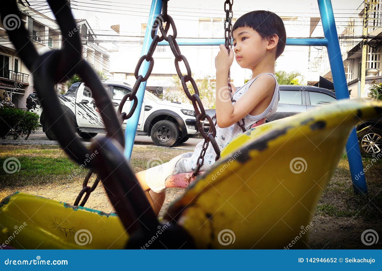 BANGKOK, THAILAND - MAART 24: De niet geïdentificeerde jongen zit op een schommeling die door kettingen in de speelplaats van het