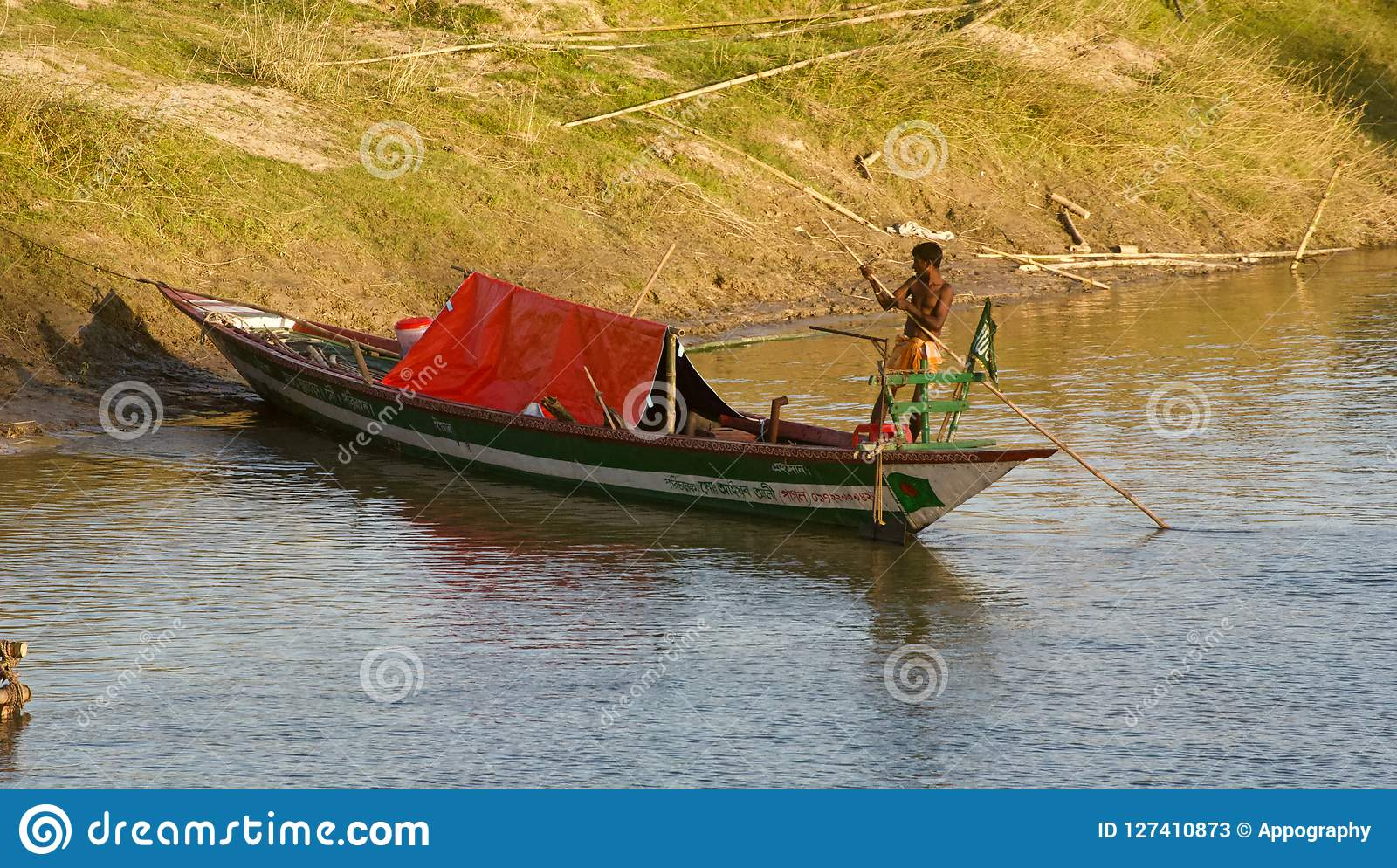 Man on a small boat around a river bank area