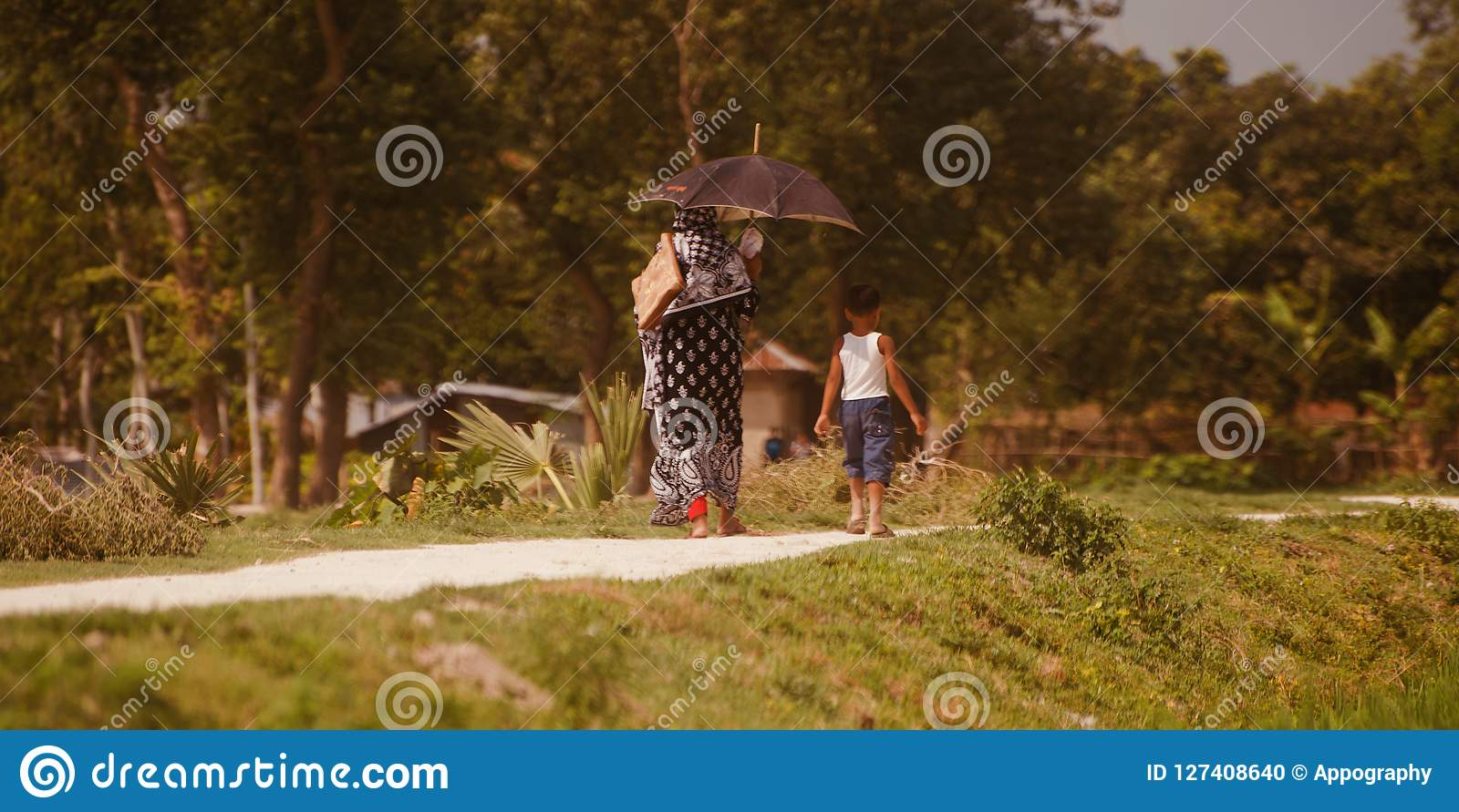 An woman and a kids walking in a village road unique photo