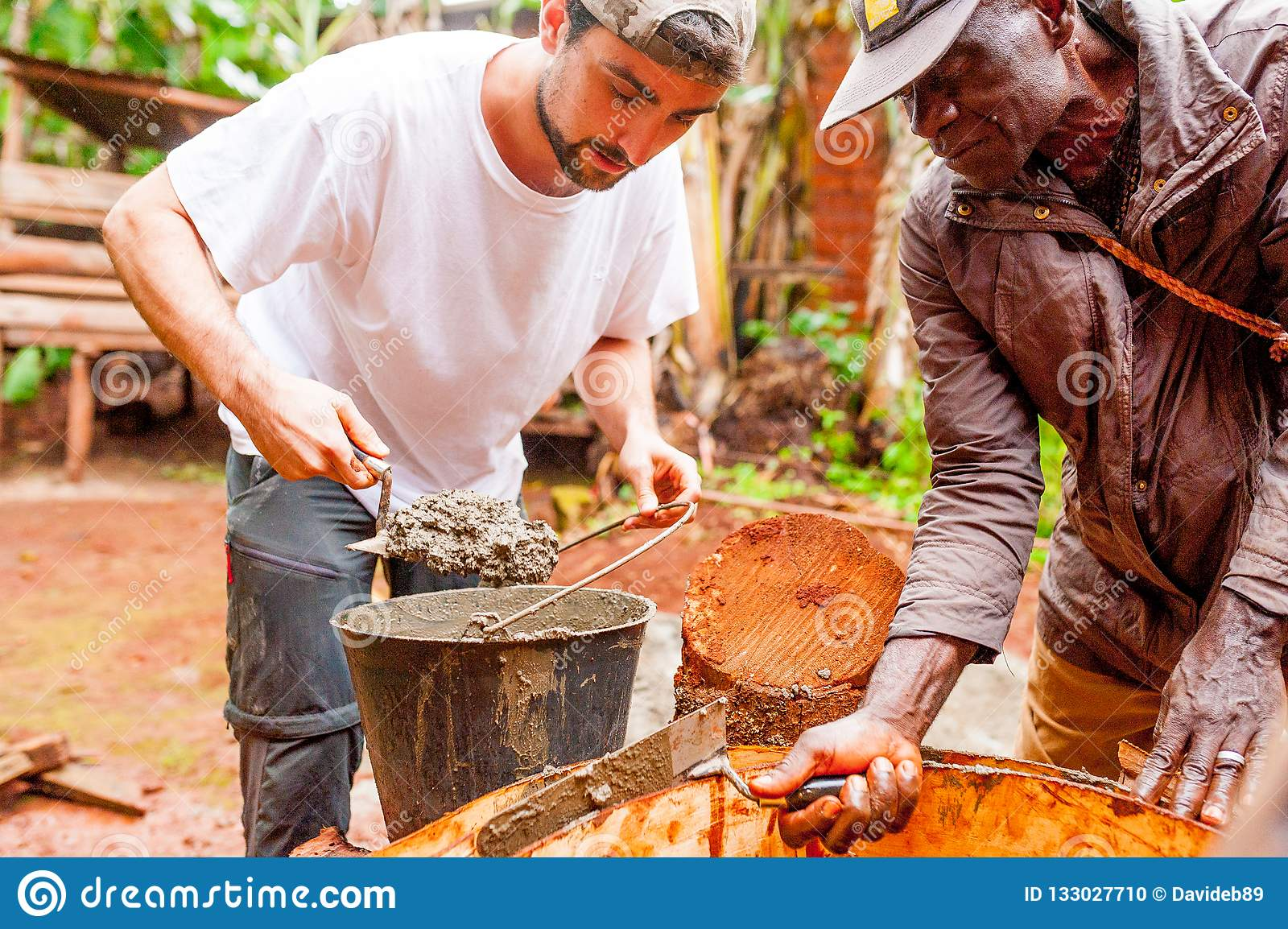 Bangoua, Cameroon - 08 august 2018: young european man in african village doing manual work building water well with concrete in