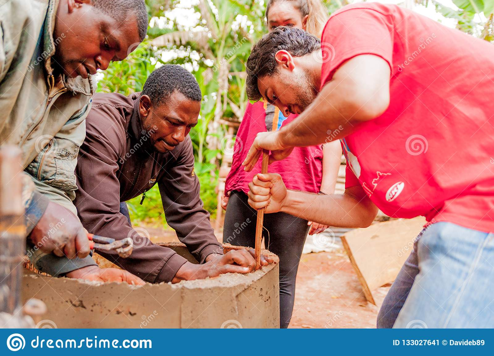 Bangoua, Cameroon - 08 august 2018: young european volunteer in african village building water well with spatula and concrete in