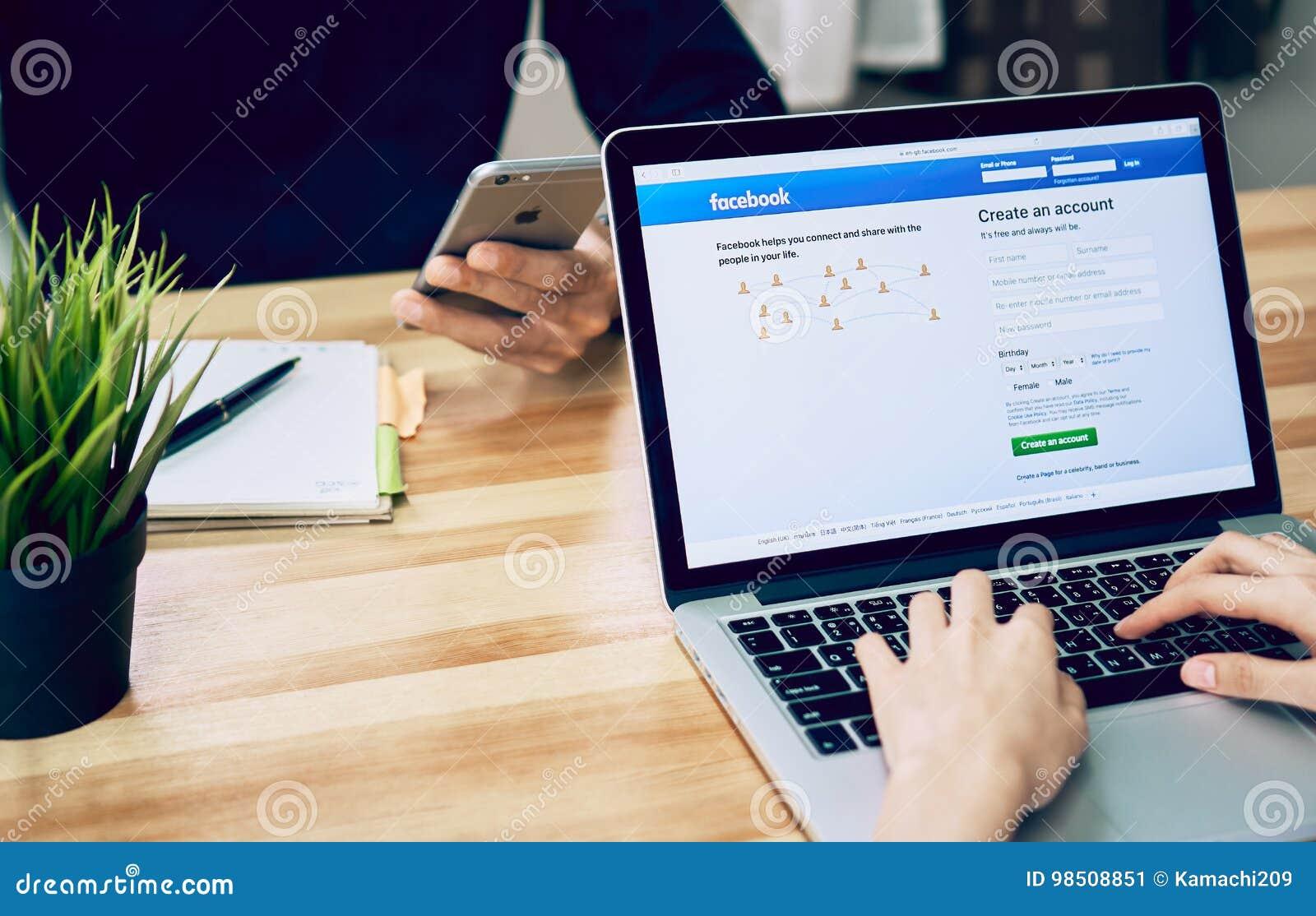 Banguecoque, Tailândia - 23 de agosto de 2017: A mulher está jogando o portátil que mostra o facebook da tela o social o maior e