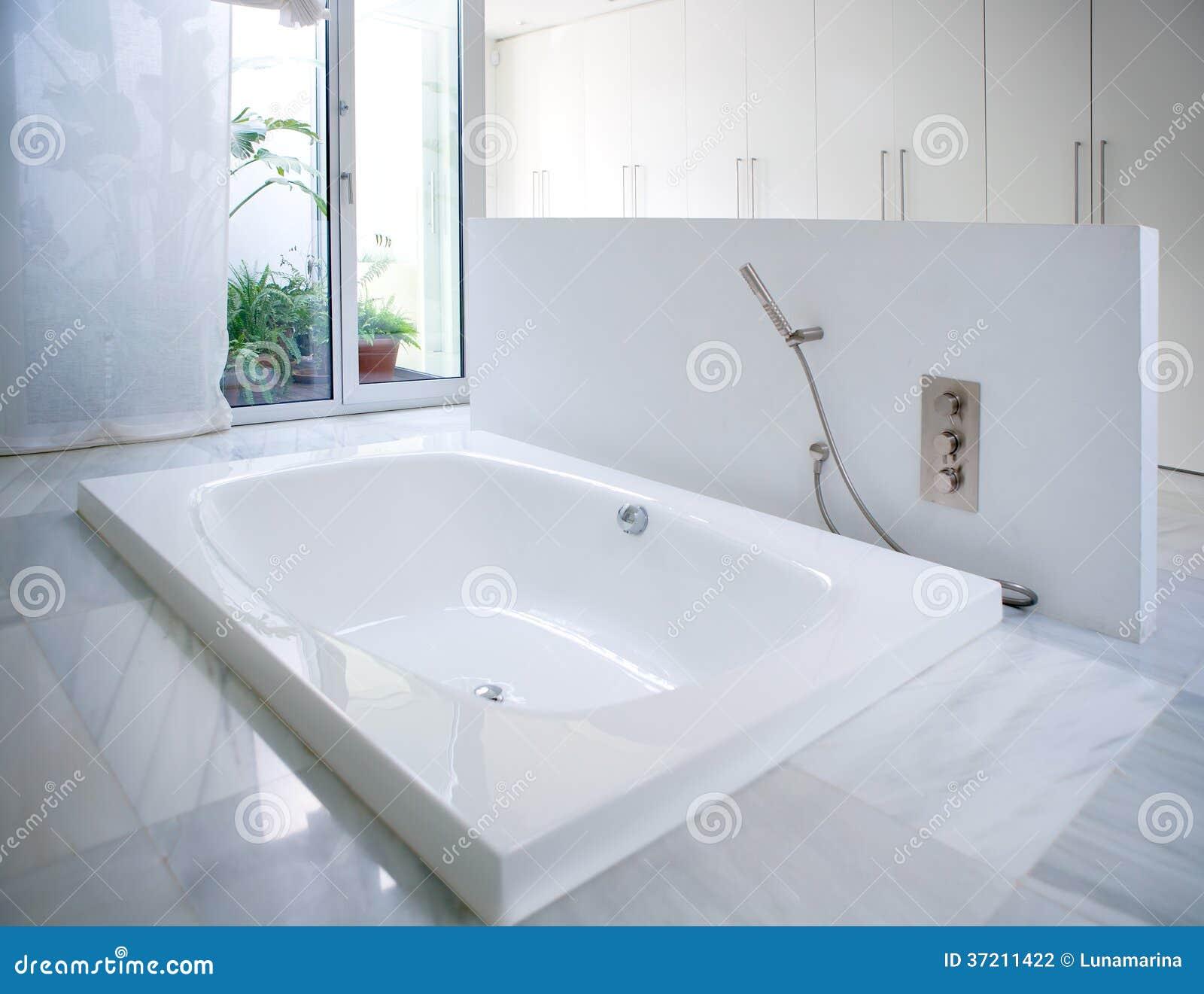 Banheira branca moderna do banheiro da casa com assoalho e a claraboia  #81A229 1300 1091
