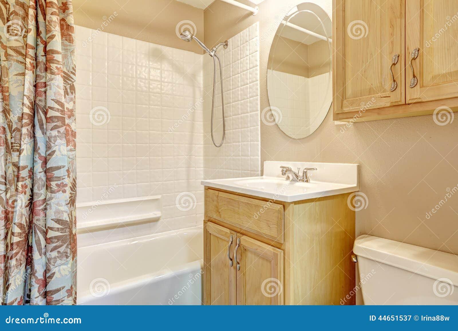 Banheiro Bege Claro Com Armários De Madeira E A Cortina Floral Foto  #793F1D 1300x957 Banheiro Com Banheira Bege