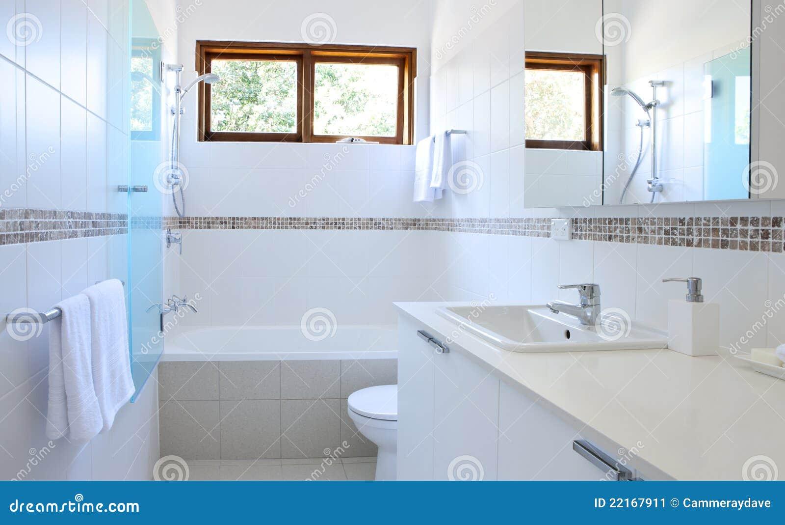 Um banheiro branco moderno com banheira dissipador tela de chuveiro  #82A229 1300x885 Banheiro Branco Moderno
