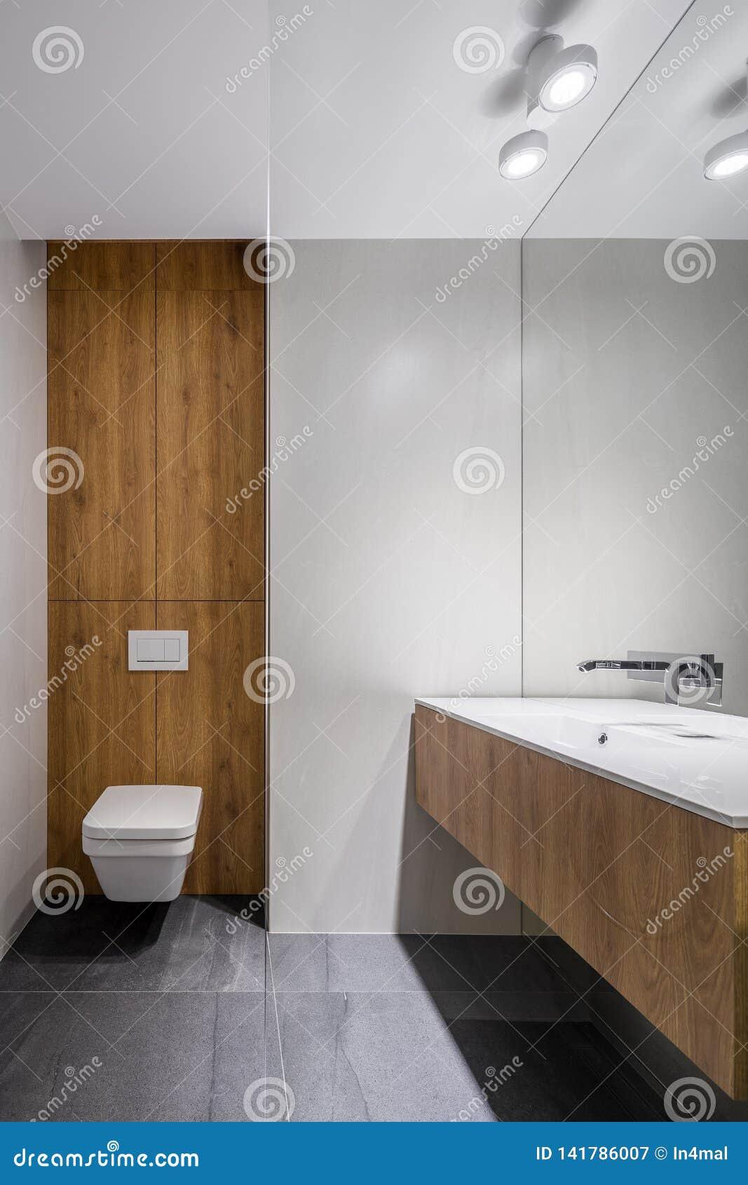 Banheiro branco com detalhes de madeira