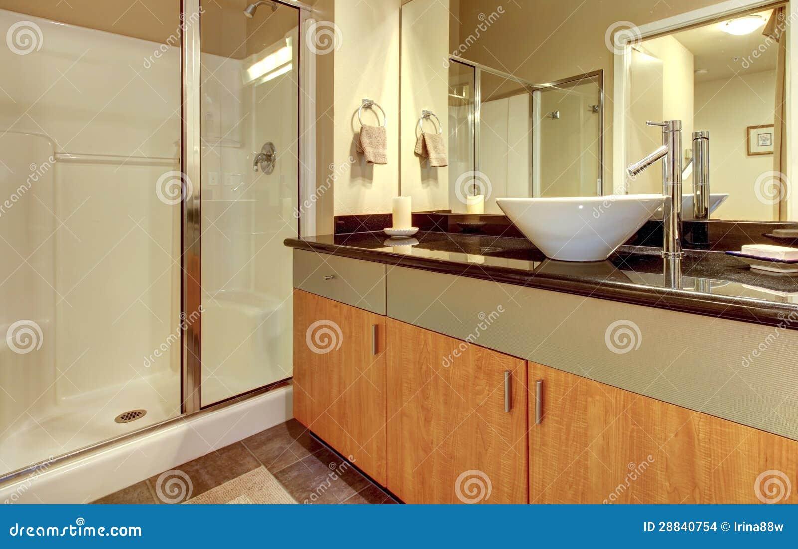 Banheiro com os gabinetes modernos de madeira o chuveiro de vidro e o  #82A229 1300 912