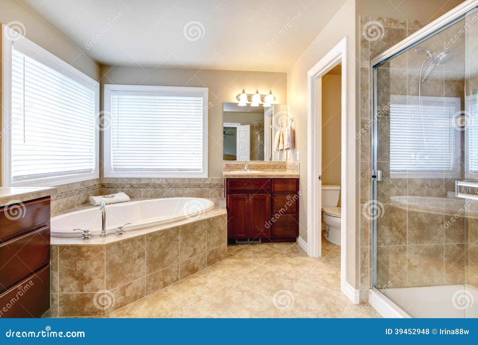 Banheiro bege com janelas os armários de madeira da cereja o  #421912 1300x957 Banheiro Com Banheira Bege