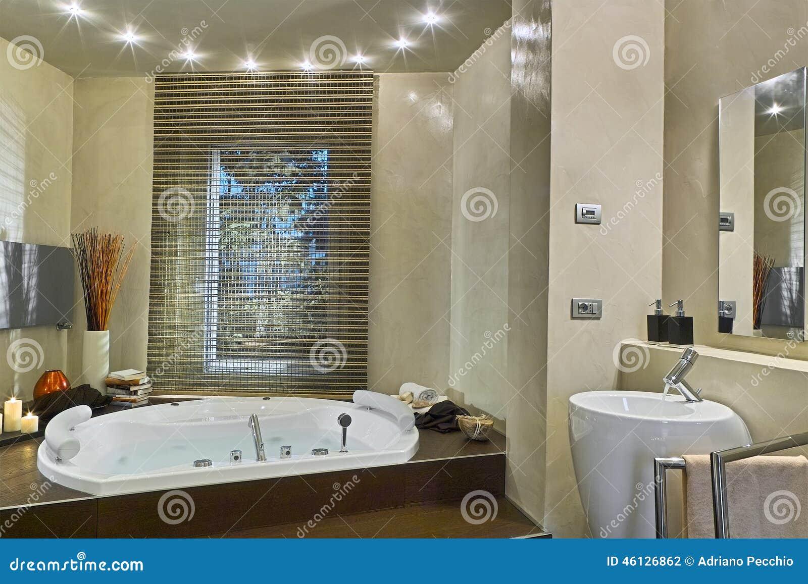 Vista interna do banheiro moderno cuja à banheira está completa da  #83A328 1300 957