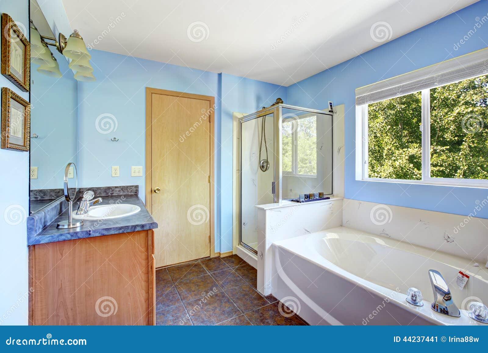 Interior do banheiro com paredes e o assoalho de telha azuis da  #6F452B 1300x957 Banheiro Com Luz Azul