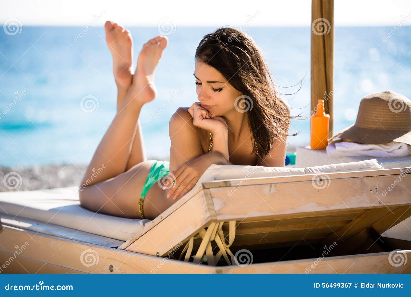 Banho de sol bonito de sorriso da mulher em um biquini em uma praia no recurso tropical do curso, apreciando férias de verão Jove