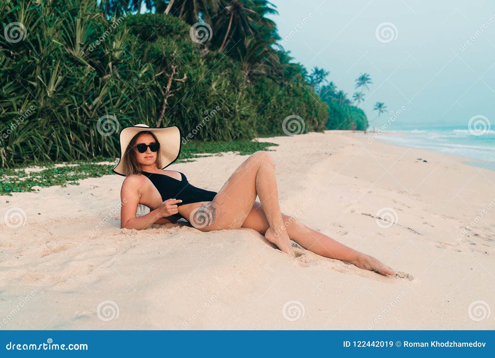 Banho de sol da menina que encontra-se na areia contra um Sandy Beach e uma selva brancos Absolutamente um aprecia seu resto, ves