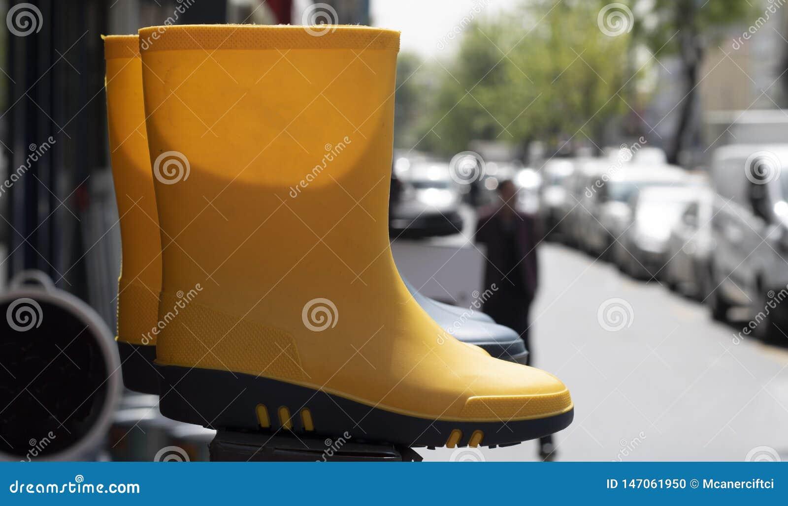 Bank die zich op de bestrating bevinden Gele laarzen