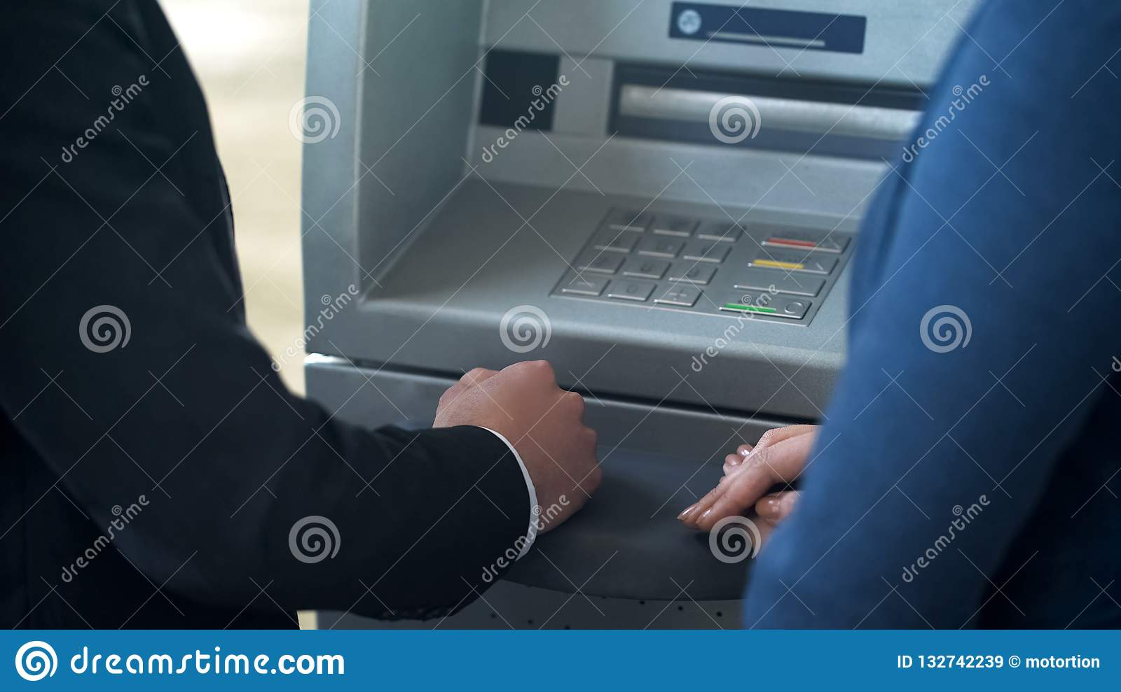 Bank employee showing new client how to work with ATM, good service technologies
