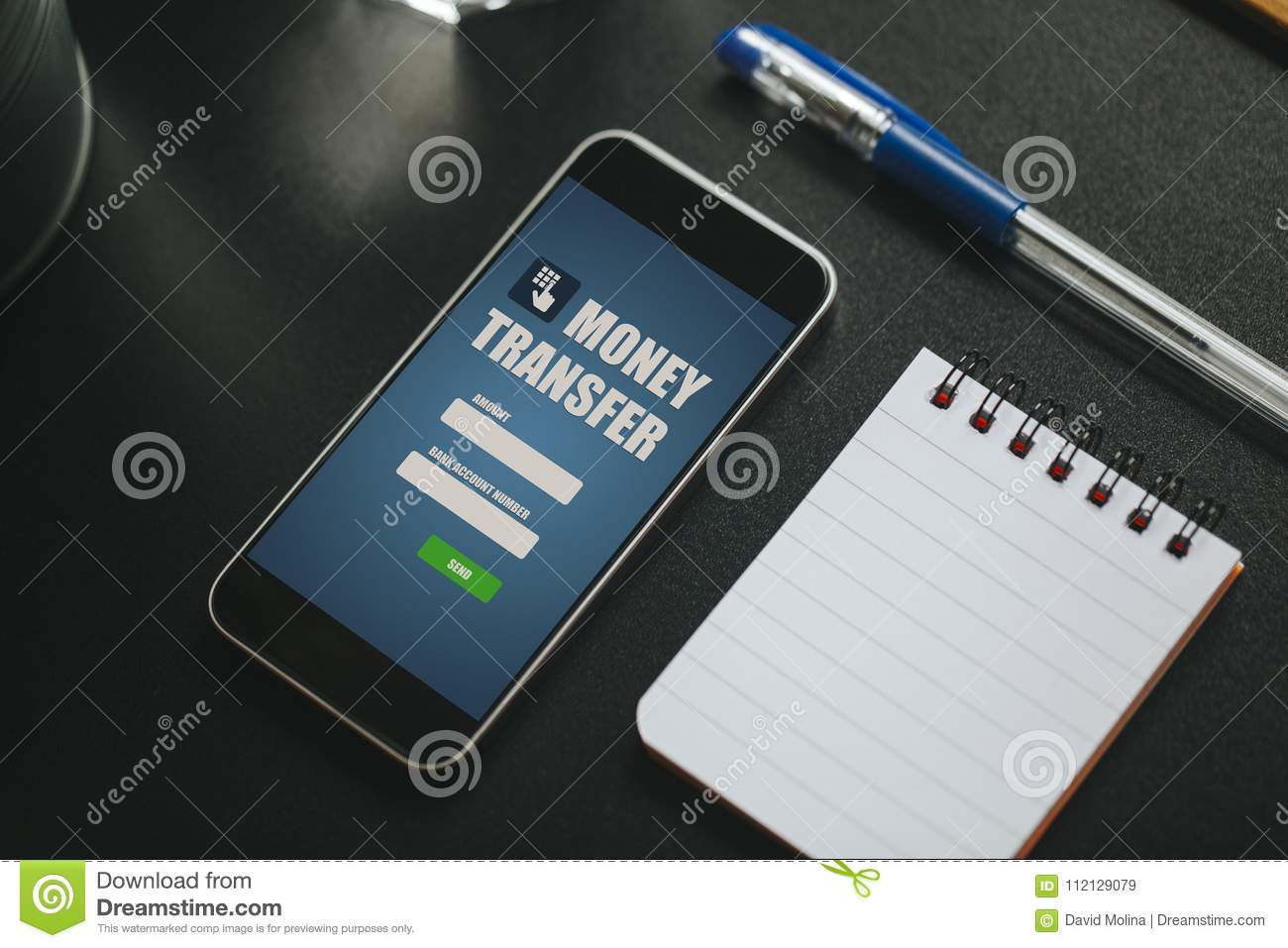 Money transfer app in a mobile phone screen over a black business download money transfer app in a mobile phone screen over a black business table stock reheart Images
