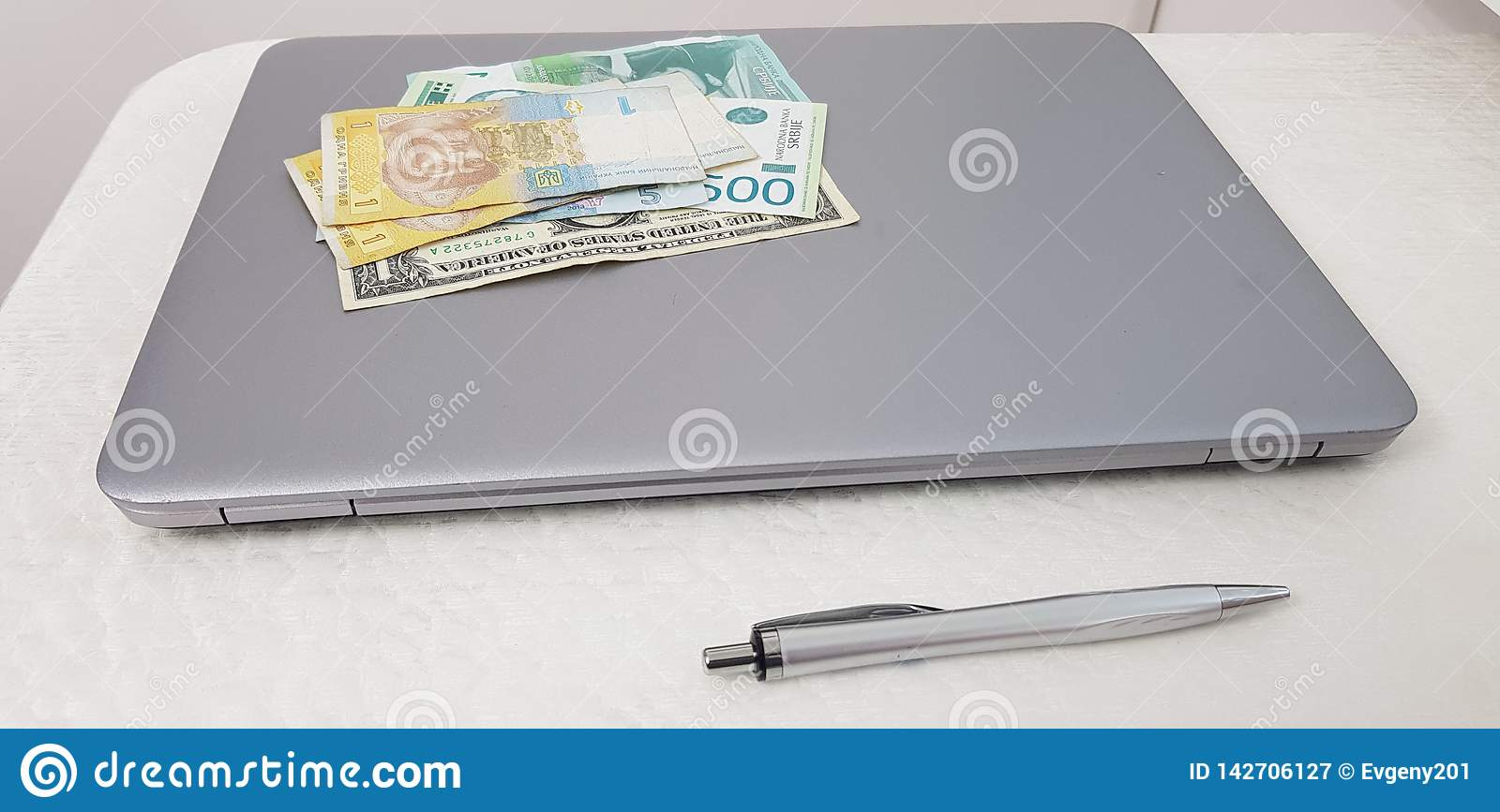 Banknotes of hryvnia dynars and dollars lay on top of laptop computer