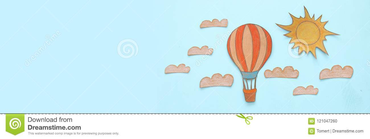 Banner of Hot air balloon, space elements shapes cut from paper and painted over wooden blue background.