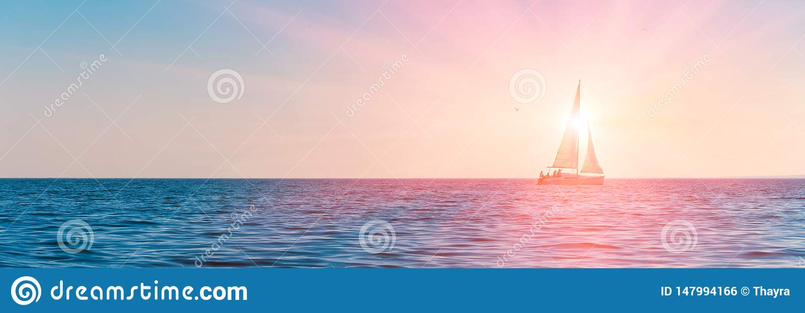 Banner 3:1. Sailboat in the sea in the evening sunlight over sky background. Luxury summer adventure or active vacation concept.