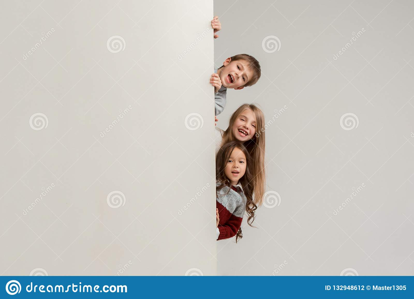 df1e587c0c1 Banner with a surprised children peeking at the edge with copyspace. The  portrait of cute little kids boy and girls looking at camera against white  studio ...