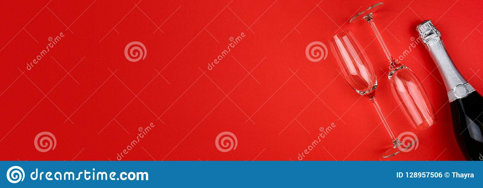 Banner 3:1 for Web. Wineglasses and bottle of champagne lying on red paper background. New Year celebration concept.
