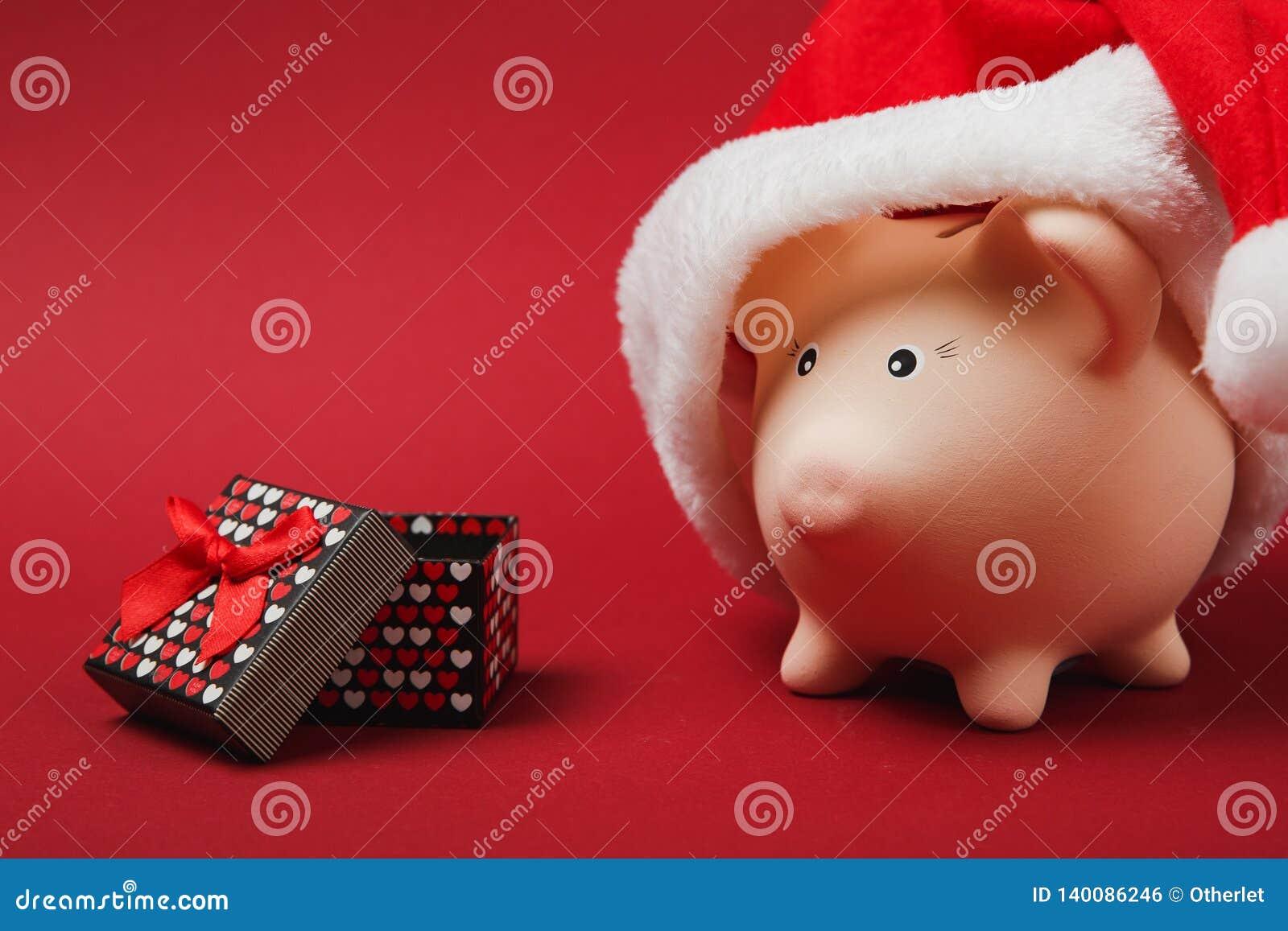 Banque porcine rose d argent avec le chapeau de Noël, boîte actuelle avec le ruban de cadeau sur le fond rouge Accumulation d arg
