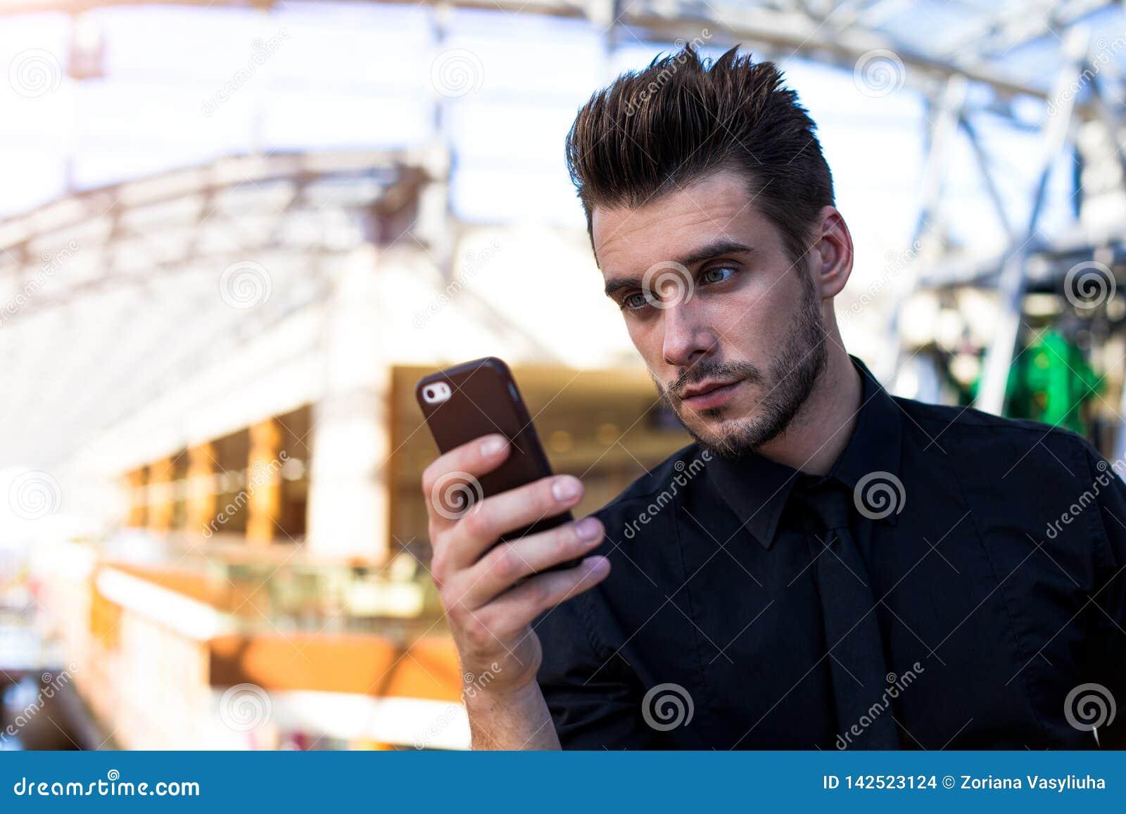 Banquero profesional barbudo que usa el teléfono móvil