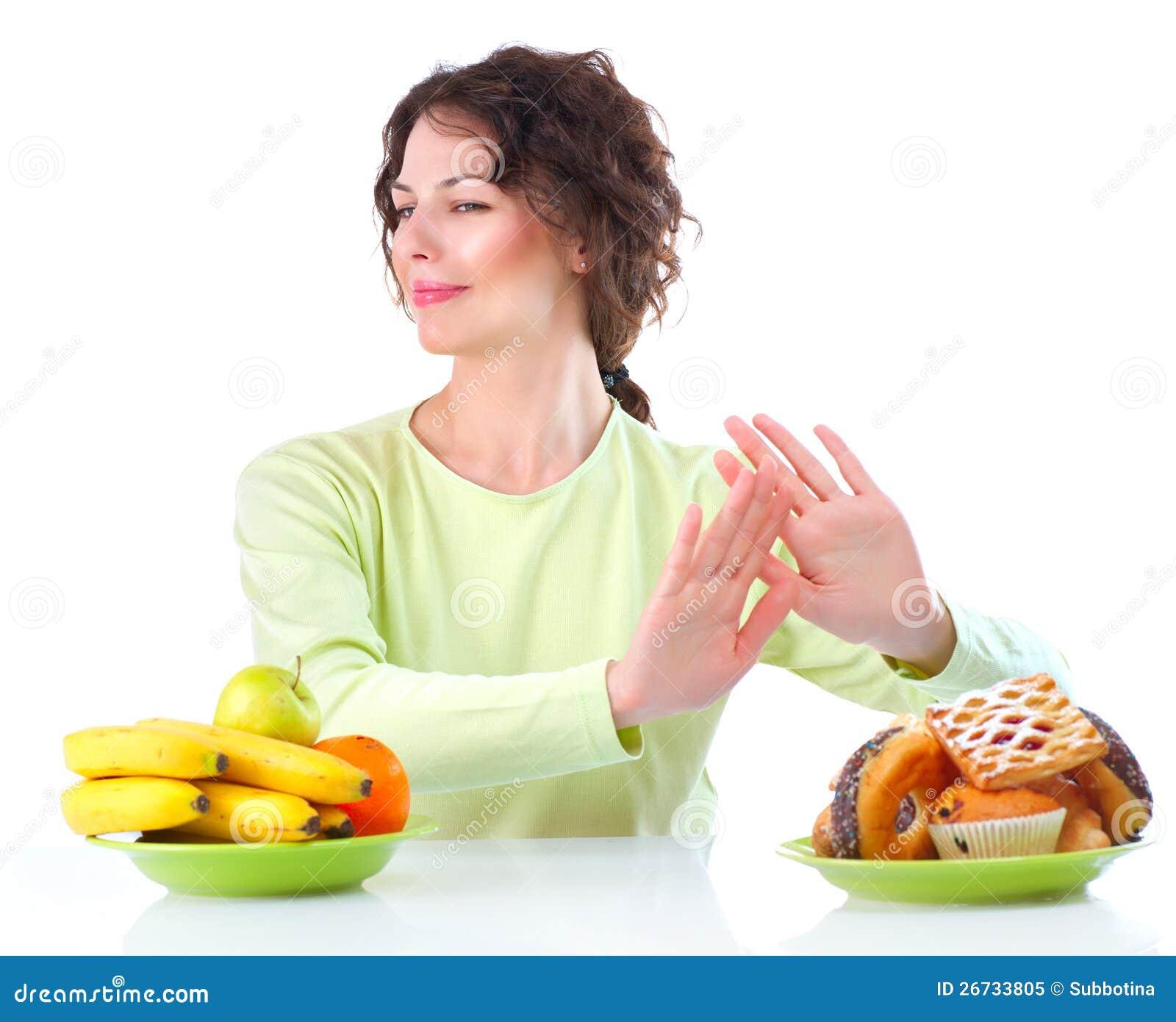 Banta. Kvinna som väljer mellan frukter och sötsaker