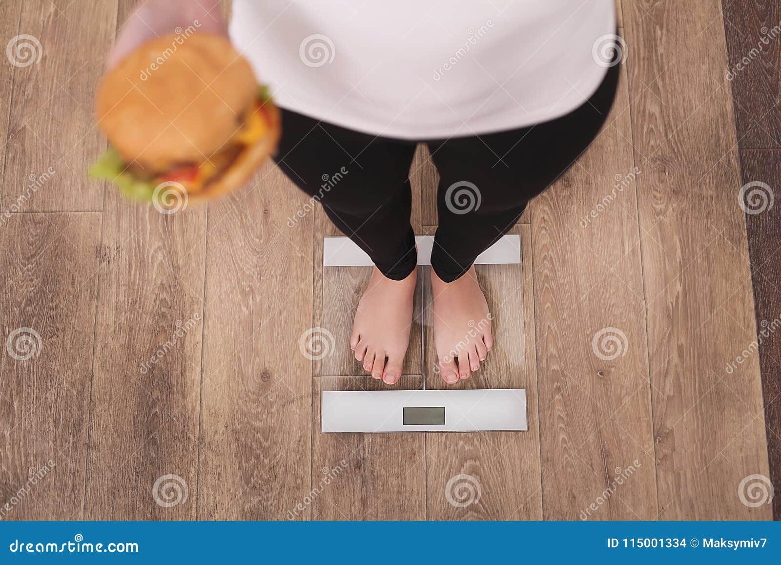 Banta och snabbmatbegreppet Överviktigt kvinnaanseende på hamburgaren för hamburgare för vägningsskala den hållande Sjuklig skräp
