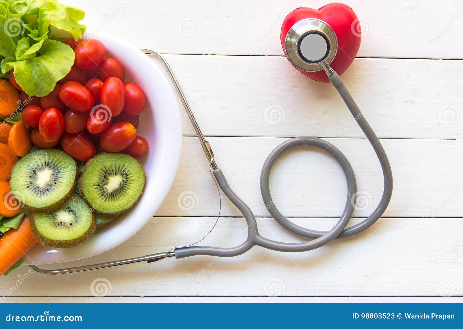 Banta och viktförlust för sund omsorg med den medicinska stetoskopet, med sallad för röd hjärta och för den nya grönsaken och sun
