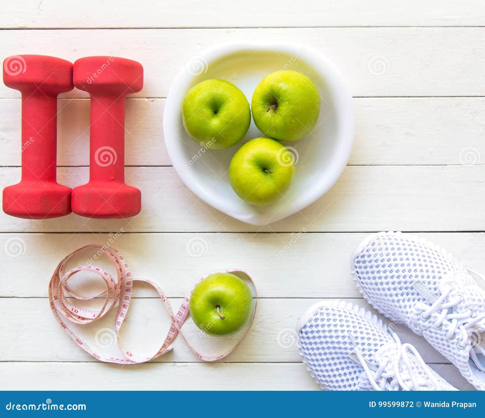Banta och viktförlust för sund omsorg med konditionutrustning, sötvatten och bära frukt sunt, äpplet - grönt äpple, på vit träbac