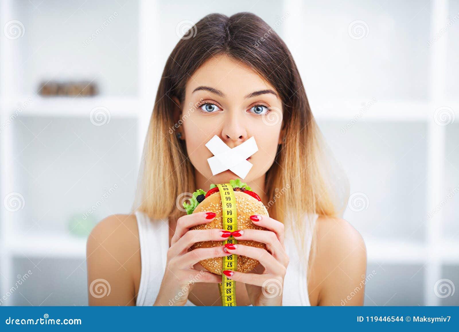 Banta Ung härlig kvinna som äter hamburgaren, det skräp för ` s och unhealt