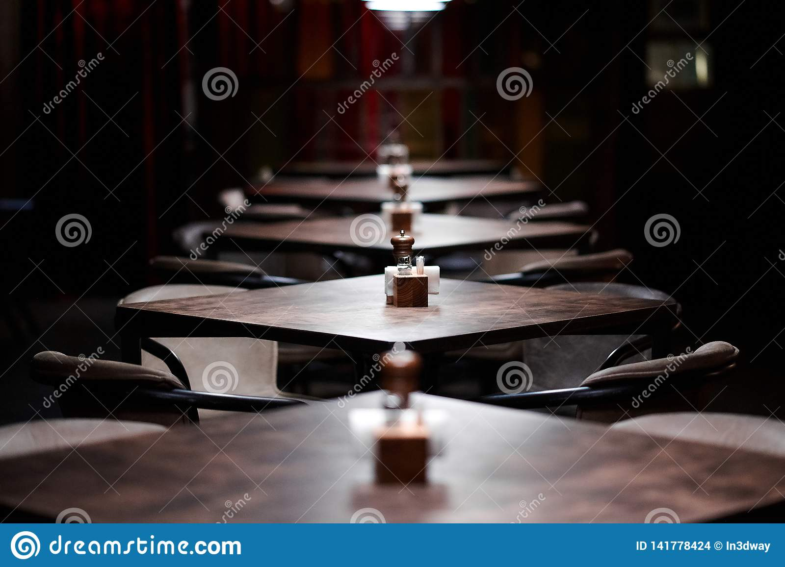 Bar wooden tables in a row, with pepper, salt shaker, toothpicks, wipes