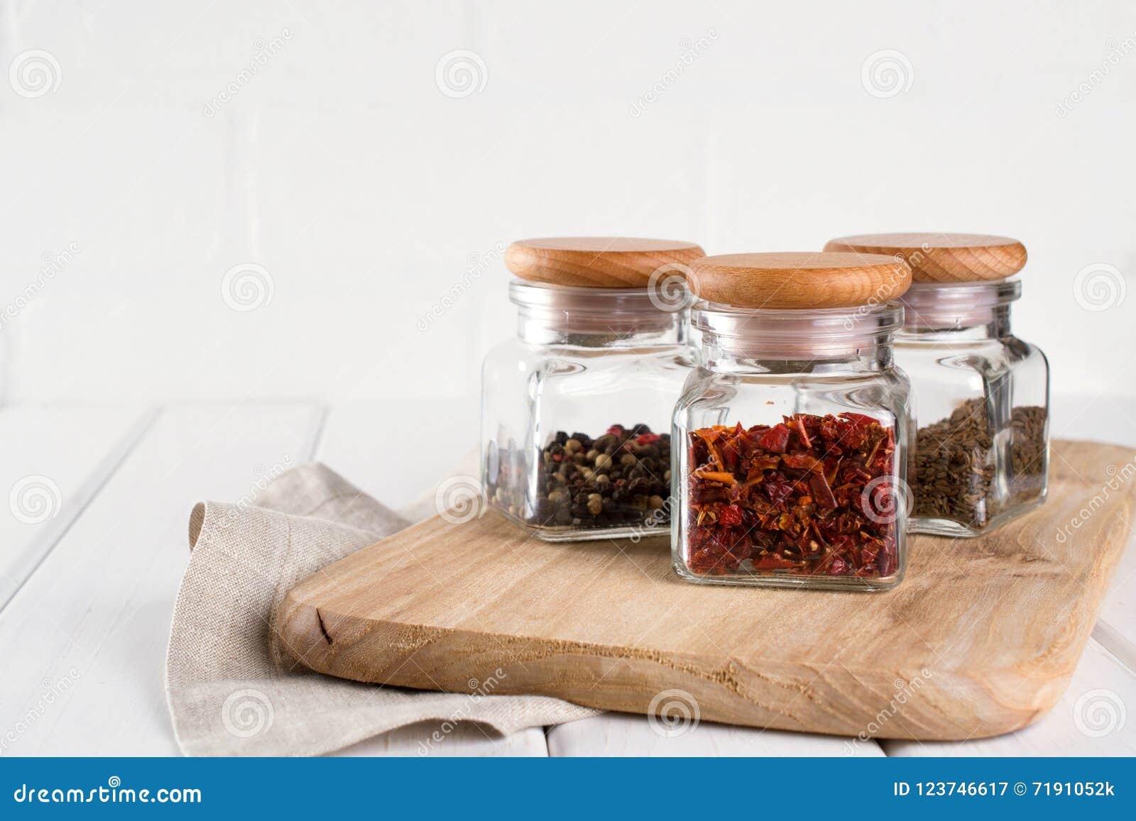 Barattoli di vetro con le spezie asciutte per cucinare