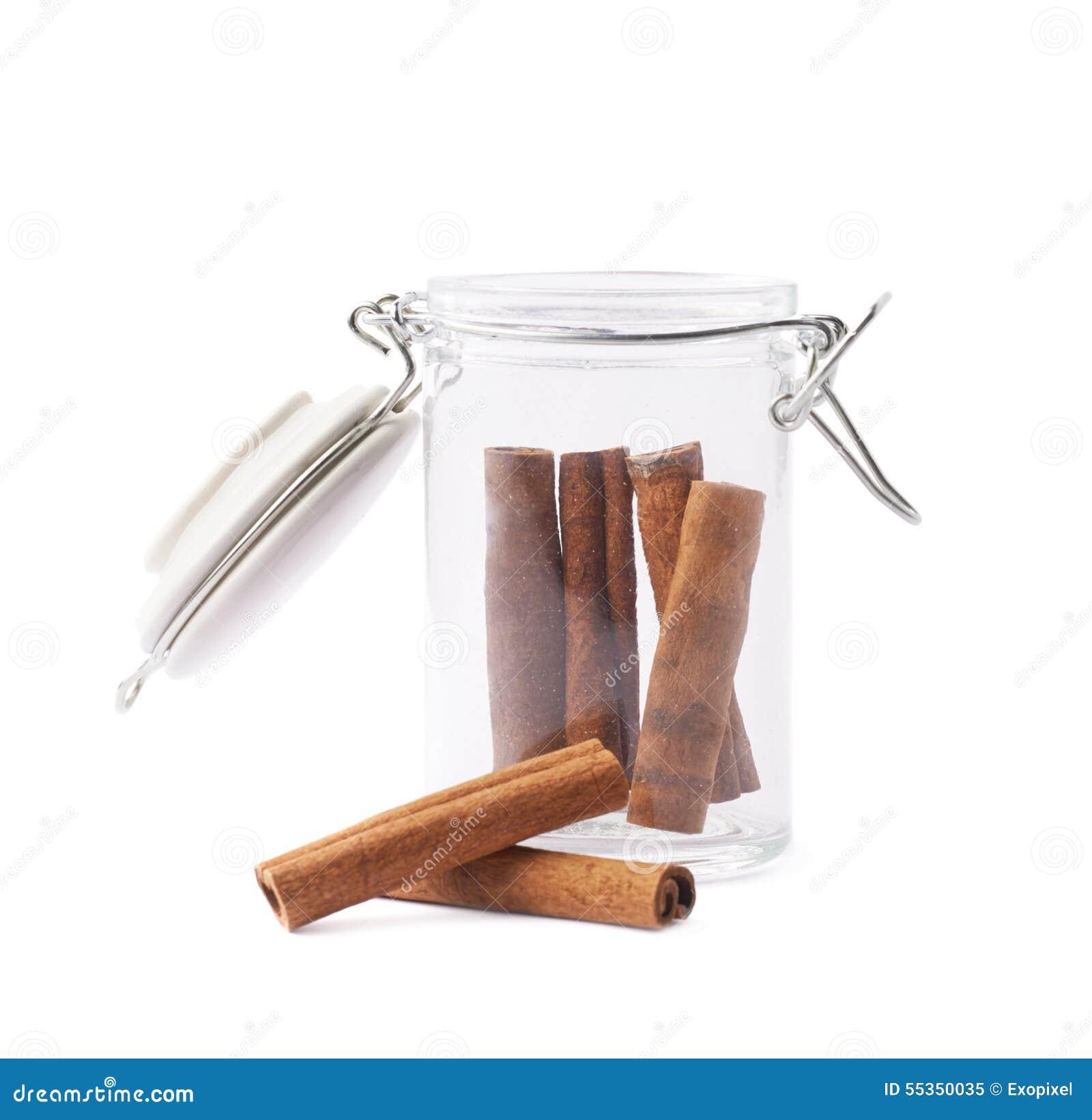 Barattolo di vetro dei bastoni di cannella isolati