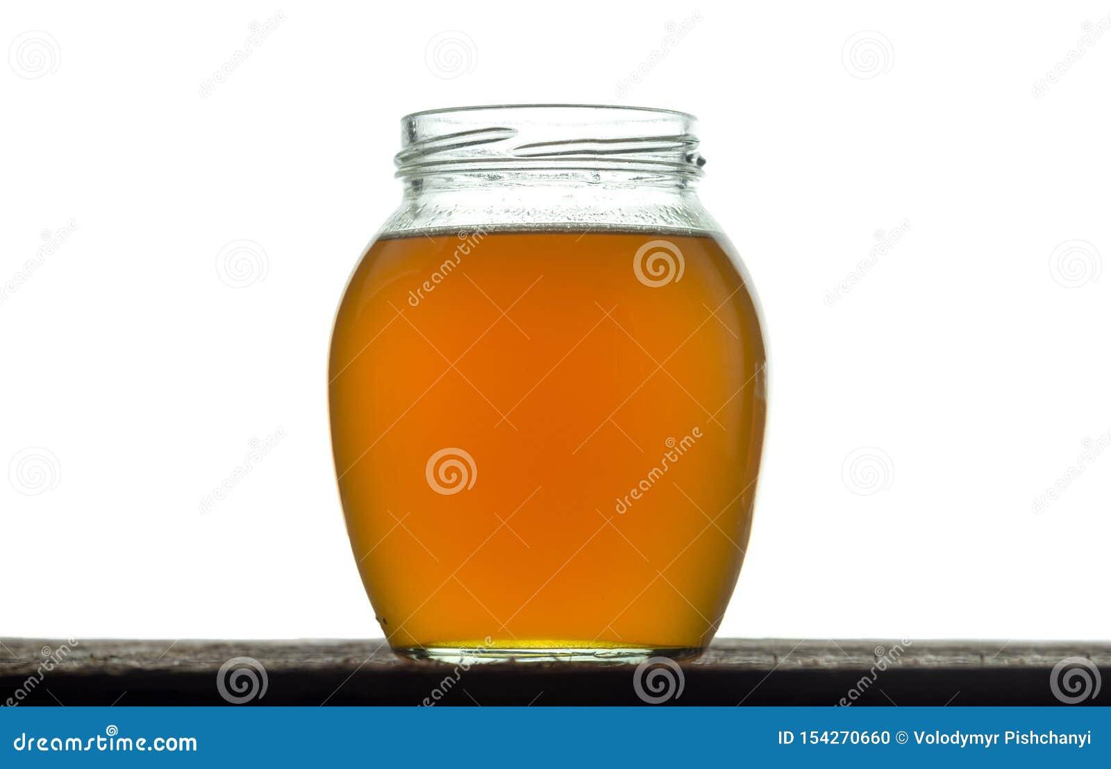 Barattolo di vetro rotondo con il burro appena preparato del ghi Su un bianco