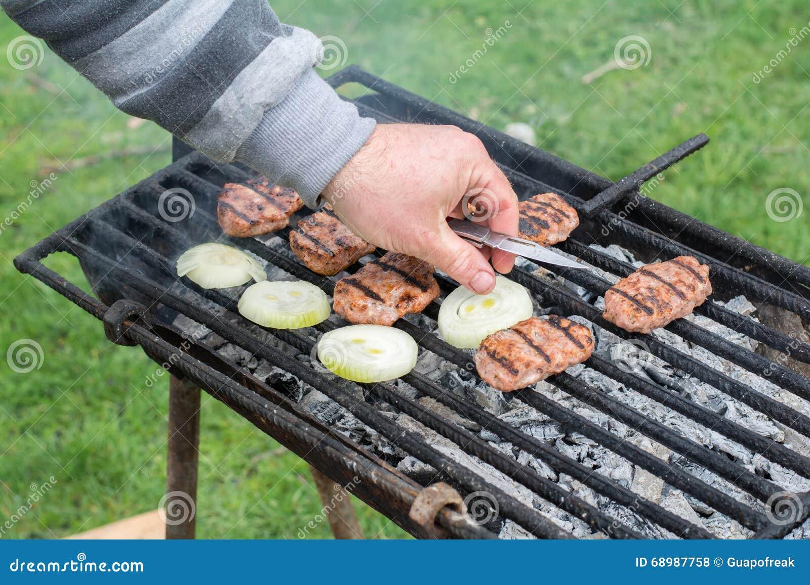 Barbacoa al aire libre Las albóndigas cocidas mano de los hombres en la parrilla