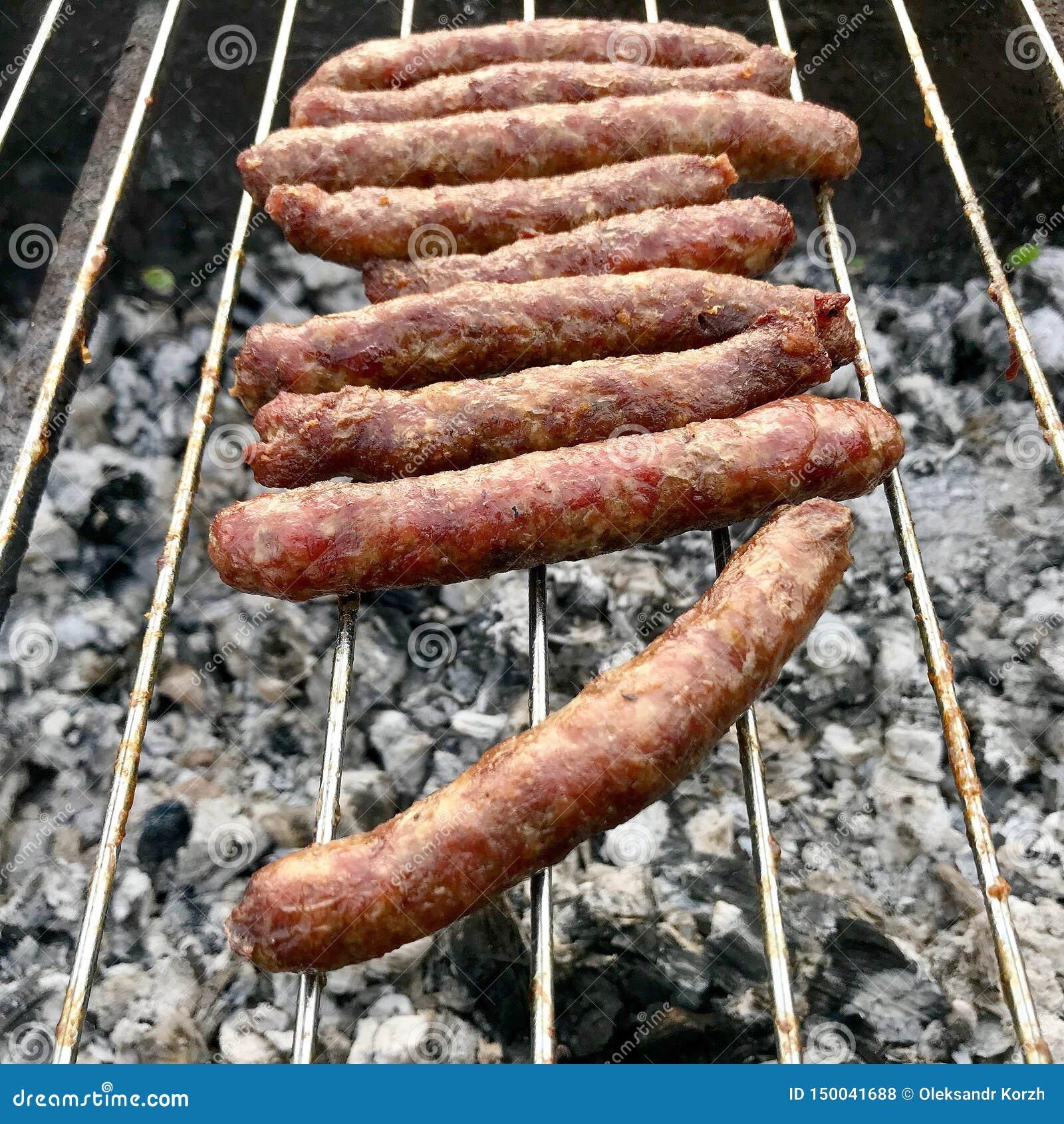 Barbacoa con las salchichas bávaras ardientes en parrilla en jardín al aire libre