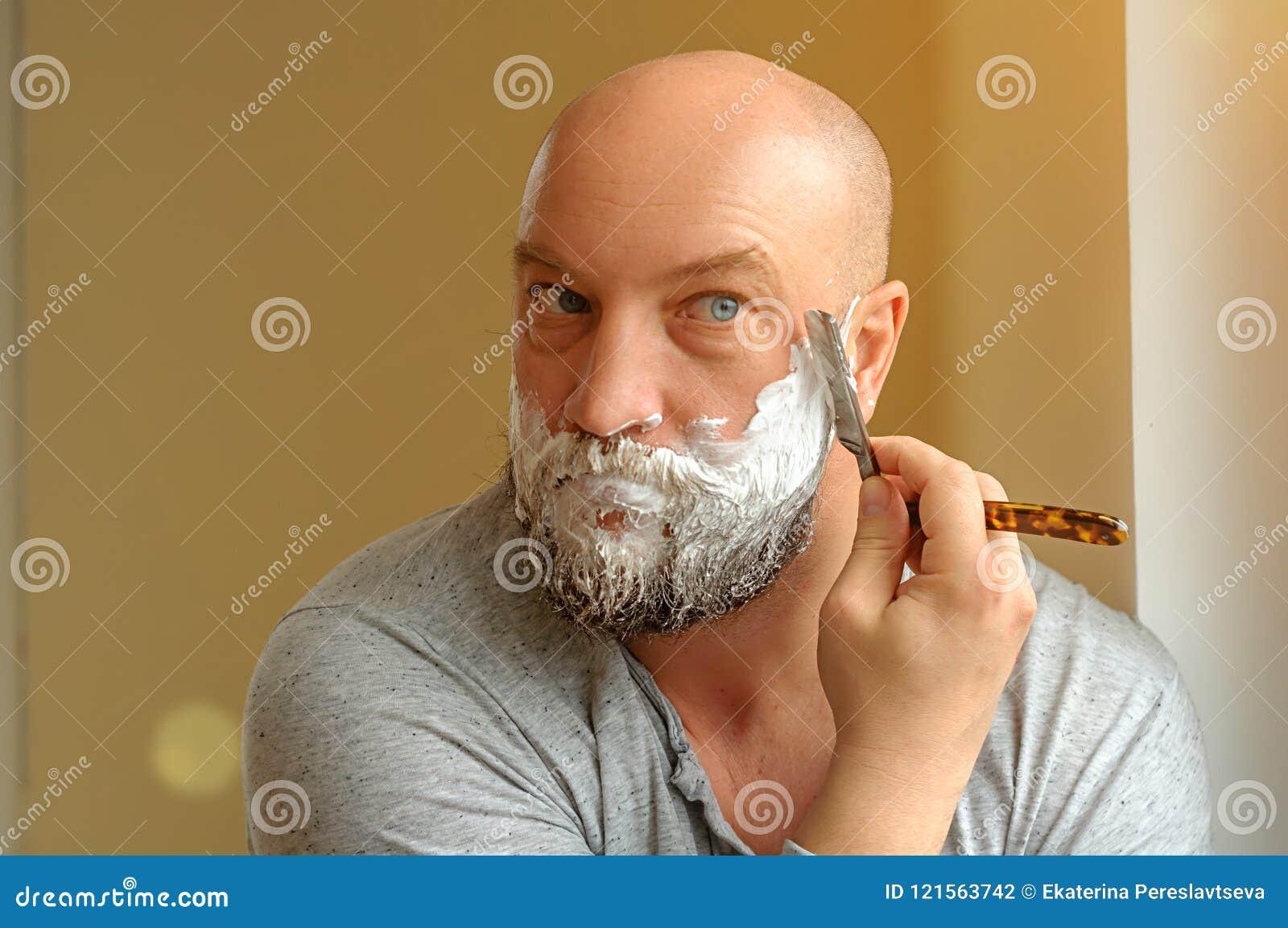Barbeações farpadas de um homem com uma lâmina reta