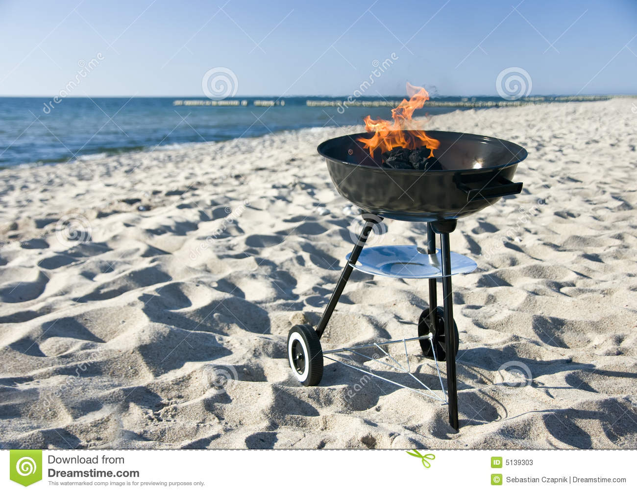 portable barbecue on a beach, the flame burning in it.MORE BEACH ...