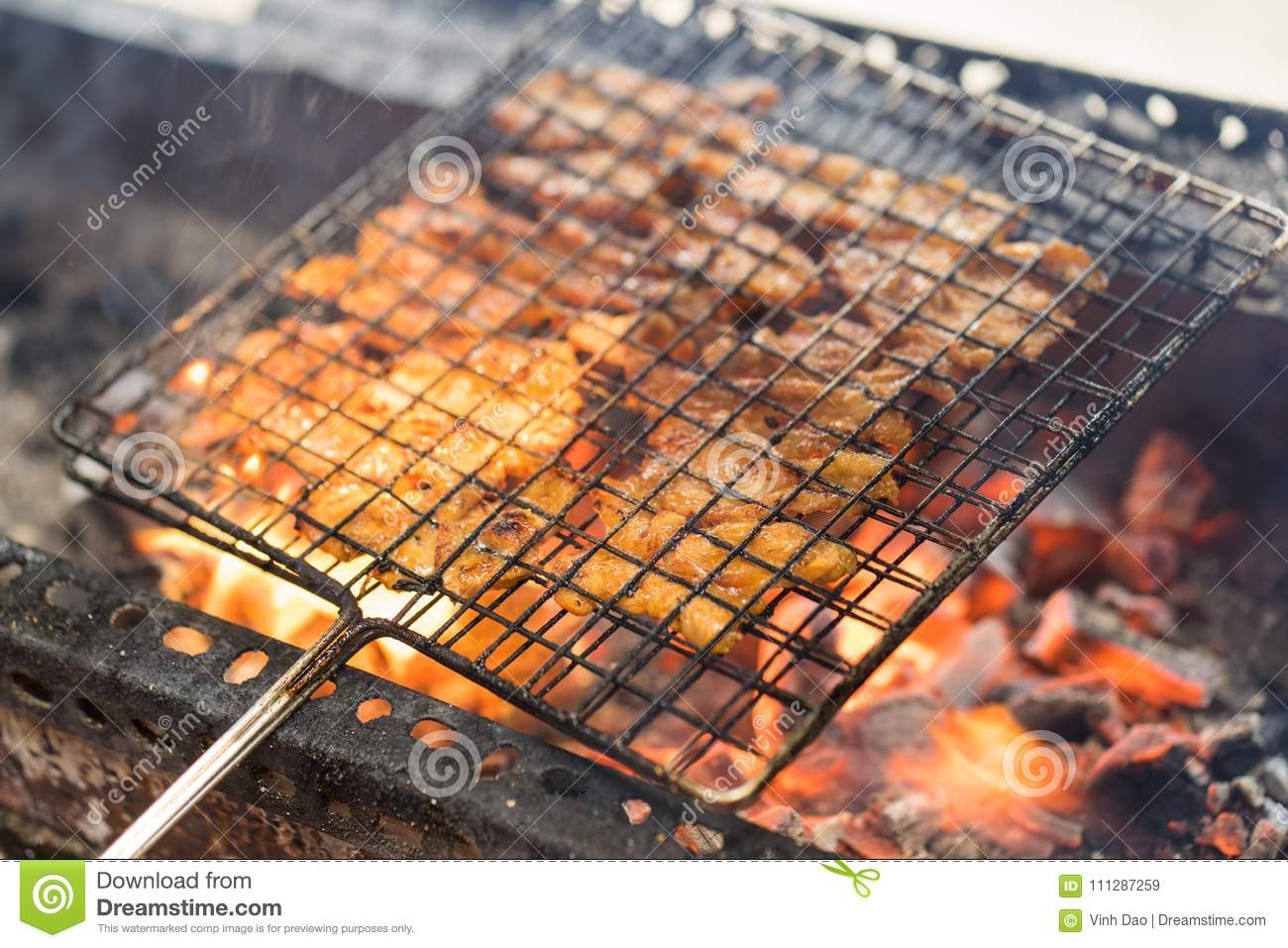 Barbecue meat cooking on fire - the ingredient of bun cha the famous Vietnamese noodle soup with bbq meat, spring roll, vermicelli